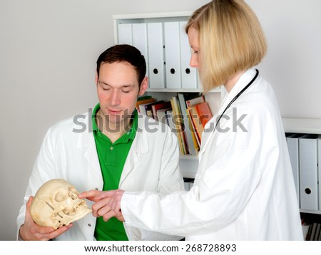 two young doctors in her office working together - stock photo