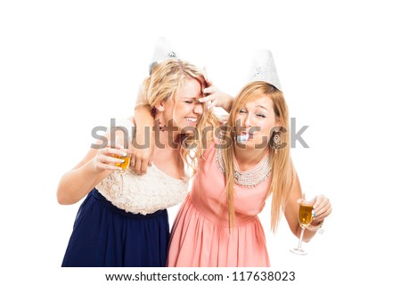 Two young drunken women celebrating with alcohol, isolated on white background. - stock photo