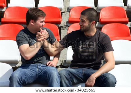 Two young fans pinch hands and enjoy the victory football team - stock photo
