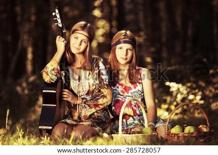 Two young fashion girls with guitar in a summer forest  - stock photo