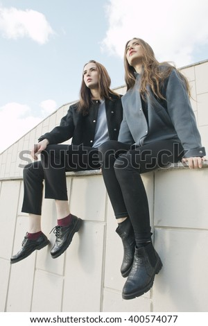 two young fashion woman sit on parapet, low angle - stock photo