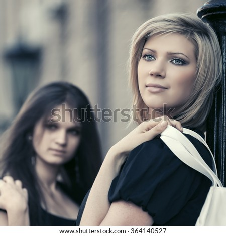 Two young fashion women on city street - stock photo
