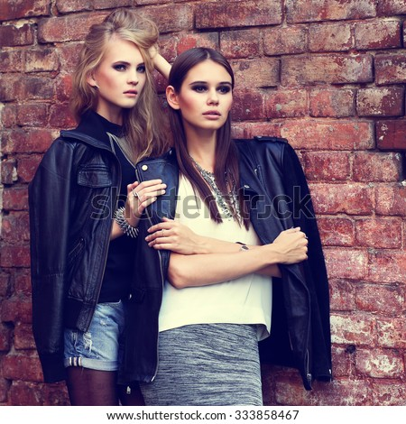 Two young fashion women outdoor. Black leather jackets, grunge style, posing near the brick wall - stock photo