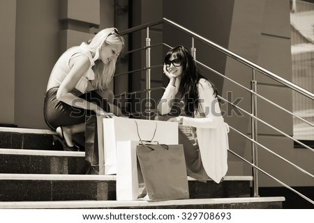 Two young fashion women with shopping bags at the mall - stock photo