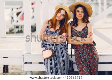 Two young  fashionable girls in straw hat and stylish summer outfit  posing  near  tropical beach bar. Soft toned image.  - stock photo