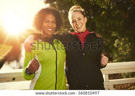 Two young female athletes hugging and looking at camera, showing they are strong - stock photo