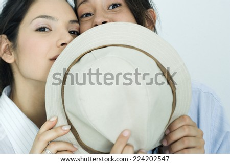Two young female friends dressed in button down shirts, looking over hat at camera, portrait - stock photo