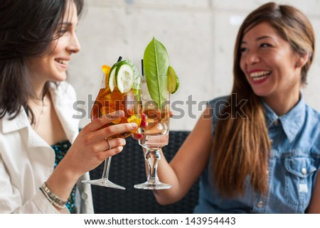 Two young female friends gossiping in a bar. - stock photo
