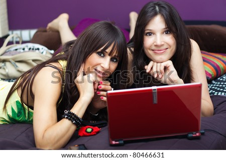 two young female friends having fun with laptop computer - stock photo