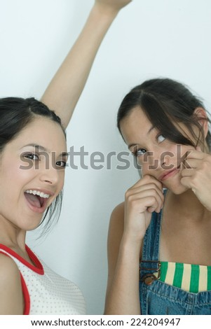 Two young female friends, one shouting with arm up, the other pulling on cheeks, looking up, portrait - stock photo