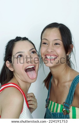 Two young female friends, one sticking tongue out, the other laughing, portrait - stock photo