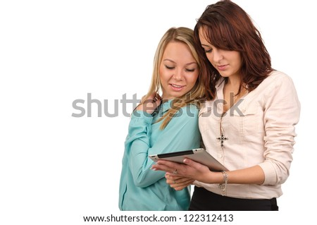 Two young female friends standing close together looking at the screen of a tablet which one of them is holding, isolated on white with copyspace - stock photo
