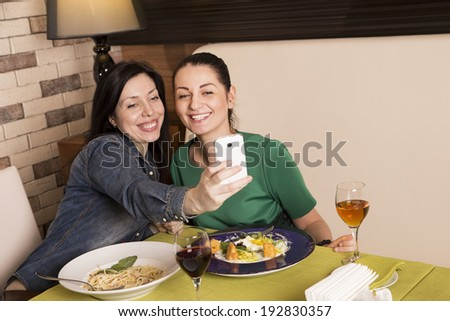Two young female friends taking a picture of themselves on a smart phone. Dinner in cafe - stock photo