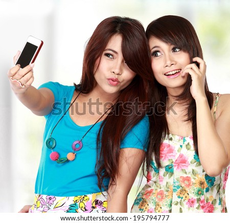Two young female friends taking a picture of themselves on a smart phone. selfie - stock photo