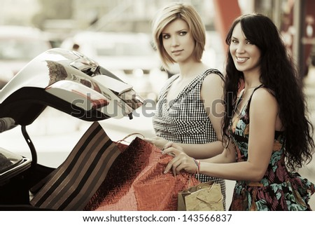 Two young female shoppers on the car parking - stock photo