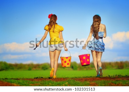 Two young females walking with  buckets on garden - stock photo