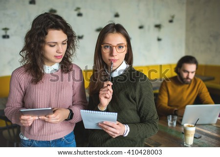Two young females with smart-phone and tablet in cafe over man with laptop - stock photo