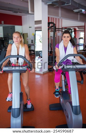 two young fit woman doing sport spinning in the gym - stock photo