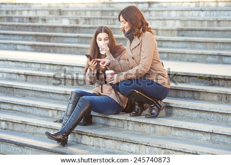Two young friends drinking coffee and chatting in front of the office building - stock photo