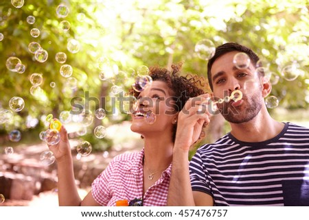 Two young friends joyfully blowing bubbles and smiling in the dappled afternoon sunshine with some trees around them wearing casual clothing - stock photo