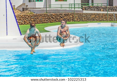 two young friends jumping in the pool - stock photo
