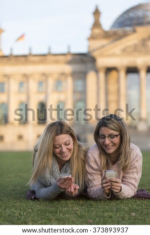 Two young friends lying down on their stomach on grass with mobile phone. On background, out of focused Parliament building (Bundestag) of Berlin - stock photo