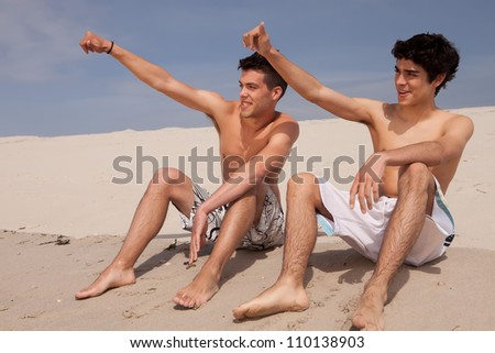 Two young friends relaxing at the beach - stock photo
