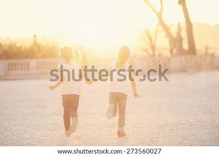 Two young friends running on a sunny afternoon - stock photo