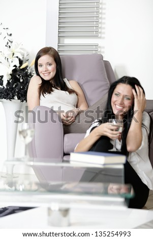 Two young friends watching television at home. - stock photo