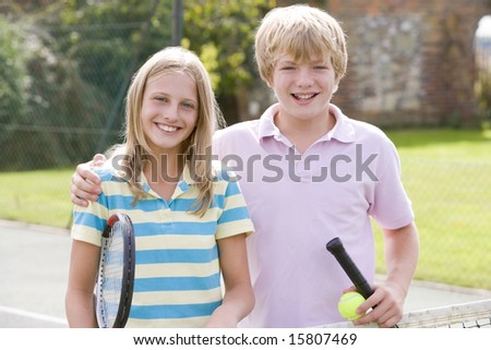 Two young friends with rackets on tennis court smiling - stock photo
