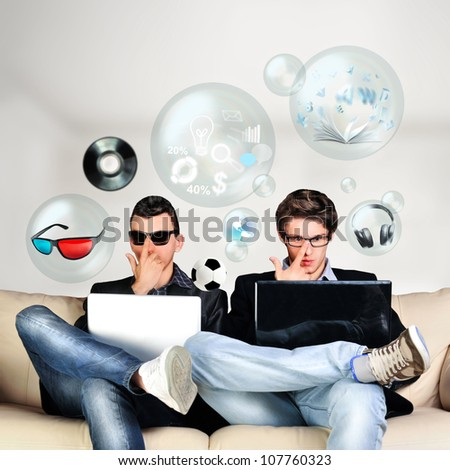 Two young gamers sitting together on sofa and using their laptops. Different objects are flying around them from laptop screen - stock photo