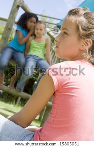 Two young girl friends at a playground whispering about other girl in foreground - stock photo