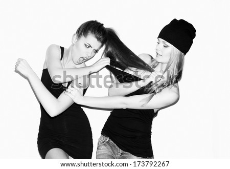 Two young girl friends having a quarrel. One keeping brunette's hair. Second pulling blonder's wear. Having fun. Casual style. Inside - stock photo