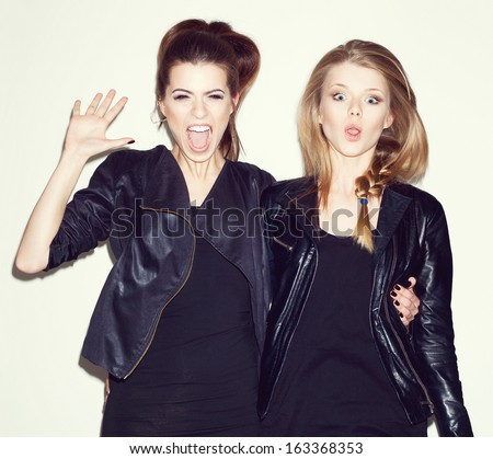 Two young girl friends having fun and jumping together. Brunette giving five her hand. Blonde making surprised face. Inside - stock photo