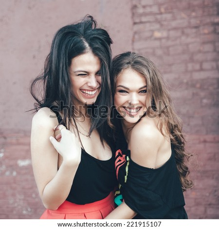Two young girl friends having fun and smiling. Outdoor lifestyle portrait - stock photo