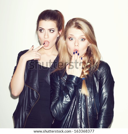 Two young girl friends having fun. Both making surprised faces. Blonde looking at camera, hand next to her lips. Inside - stock photo