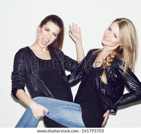 Two young girl friends having fun together. Brunette keeping blonde's leg. Both smiling and looking at camera. Inside - stock photo