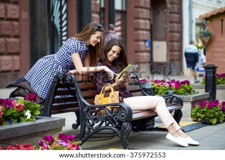 Two young girl friends sitting on a bench in the town center - stock photo