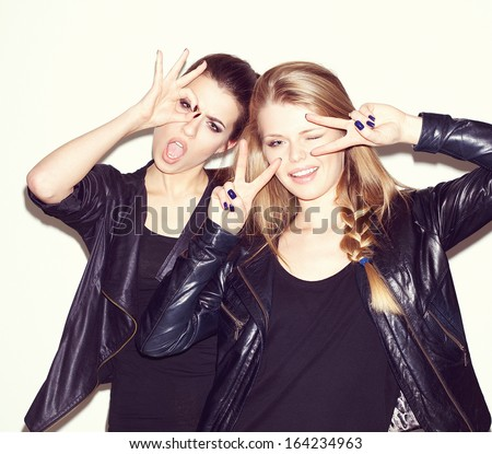 Two young girl friends standing together and having fun. Showing signs with their hands. Looking at camera and smiling. Inside - stock photo