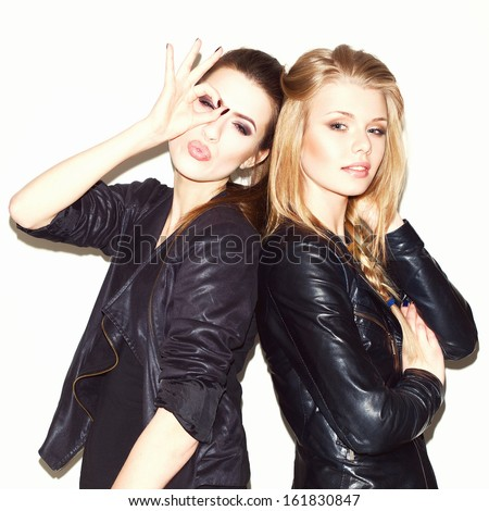 Two young girl friends standing together. Brunete having fun and showing sign with her hand. Looking at camera. Inside - stock photo