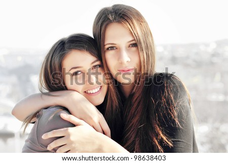 Two young girl friends together on walk - stock photo