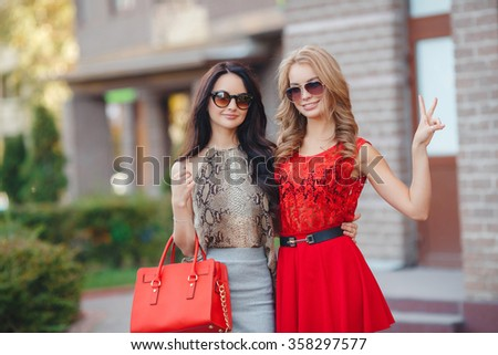 Two young girl friends together on walk. two beautiful young women having fun in the city. fashion. summer fashionable girls outdoor. Two cheerful girls sisters, in the street - stock photo
