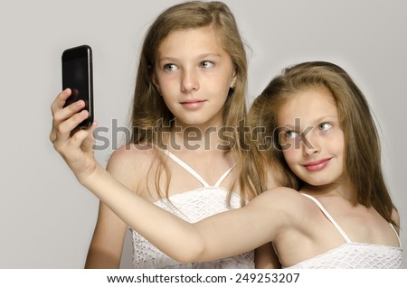 Two young girl taking a selfie, kids taking a photo and having fun, girls playing with a mobile phone - stock photo
