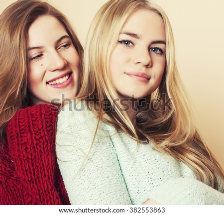 Two young girlfriends in winter sweaters indoors having fun. Lifestyle. Blond teen friends close up - stock photo