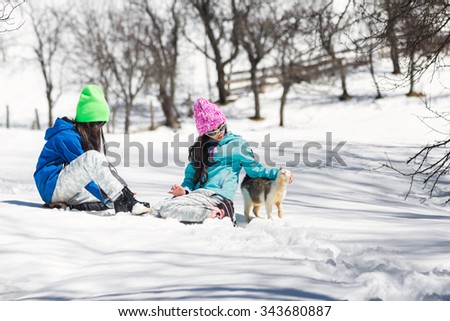 Two young girls enjoy playing in the snow with a cat - stock photo