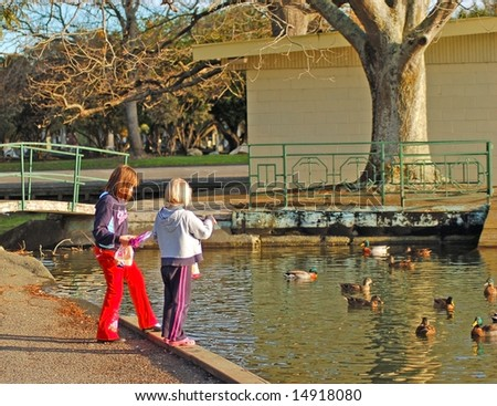 two young girls feeding ducks - stock photo