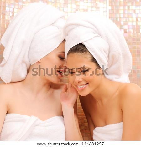 Two young girls gossiping in Turkish sauna - stock photo