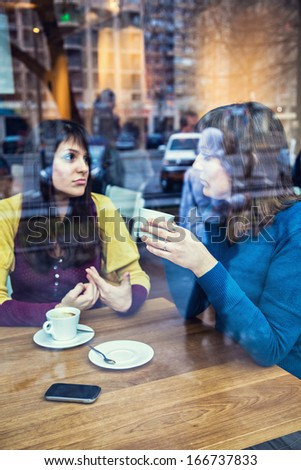 Two young girls having conversation in a cafe. The photo was taken through the window - stock photo