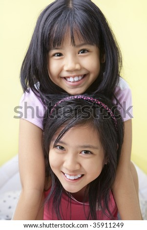 Two young girls in bedroom - stock photo