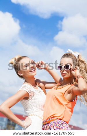 two young girls in summer outfit pose for the camera against the blue sky - stock photo
